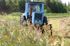 Farming tractor working in field of freshly cut during hayfield. - stock photo