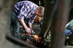 Stock Photo of Farmer repairing lawn mower in wooden barn, sharpens knives.