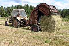 Tractor with round baler collects the hay to hayfield. - stock photo