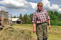 Harvest hay in Russian north, peasant tractor driver inspects hayfield. - stock photo