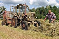 Farmers field , agronom tractor-driver at work checking fresh hay. Stock Photos