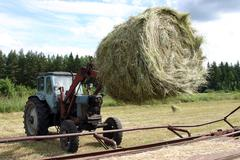 Stock Photo of Tractor with bucket forklift moves circular bale hay in trailer.
