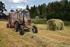 Round baler dumping a freshly rolled hay bale. Stock Photos