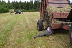 Time to hay, driver mechanic repairing roll baler in field. - stock photo