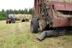 Farmer repairing round baler, in field, during hay. Stock Photos