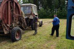 Tractor Farm Equipment Mechanics inspect in process of making hay. Stock Photos