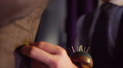 Close up on the hands of a tailor fitting a suit for a customer.  Stock Footage