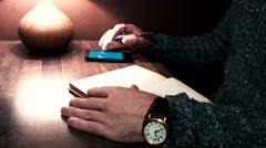 Hands on the table working on a smartphone and write a pen to notebook Stock Footage