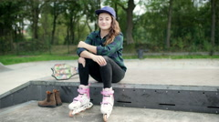 Stock Video Footage of Girl wearing rollerblades and smiling to the camera in skate park