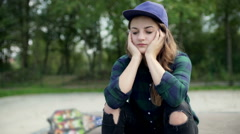 Worried girl wearing purple hat and sitting in the skatepark, steadycam shot Stock Footage