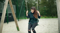 Worried girl sitting on the seesaw and swinging slowly Stock Footage