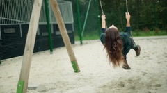 Girl swinging on the seesaw with her eyes shut and relaxing Stock Footage