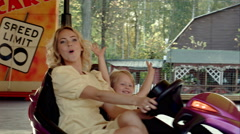 Happy mother with her daughter drive on bumper cars in Amusement park Stock Footage