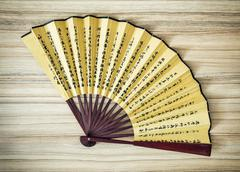 Traditional eastern fan on the wooden background - stock photo