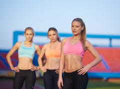 athlete woman group  running on athletics race track - stock photo