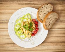 Scrambled eggs with paprika, cherry tomatoes and bread - stock photo