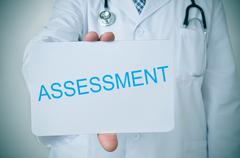 Stock Photo of doctor showing a signboard with the word assessment