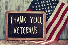 Text thank you veterans in a chalkboard and the flag of the US Kuvituskuvat
