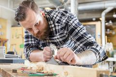 Focused carpenter work with plane on wood plank in workshop Stock Photos