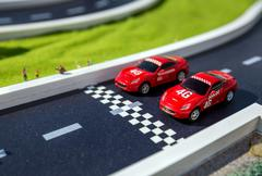 Toy sport cars on a breadboard. Two reds racing cars on race track Kuvituskuvat