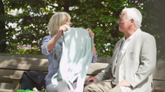 Stock Video Footage of 4K Happy mature couple with shopping bags, looking at their purchases outdoors