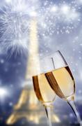 Close up on glasses of champagne, Eiffel tower and fireworks in the backgroun - stock photo