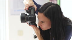 Photographer brunette girl at work shooting process take pictures with camera Stock Footage