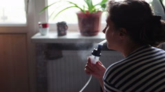 Woman wears a mask for inhalation, and conducts the procedure lungs inhalation Stock Footage