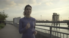 Female runner jogging by river Thames, London Stock Footage