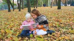 little sisters read the book in the autumn park - stock footage