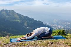 Sporty fit woman practices yoga asana Balasana Stock Photos