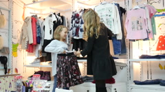 Mother and daughter in clothes shop choose a new jacket and skirt - stock footage