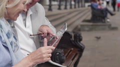 4K Portrait of happy mature couple looking at computer tablet in the city Stock Footage