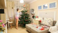 Christmas Tree decorate time lapse, young girl fuss around green fir, part 2 Stock Footage