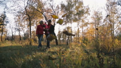 Happy family with small child walking in the autumn forest. - stock footage