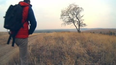 Man hiker traveler with backpack in autumn is on the way to nature is solitary Stock Footage