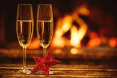 Two glasses of sparkling champagne in front of warm fireplace. C Stock Photos
