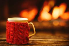 Stock Photo of Cup of hot drink in front of warm fireplace. Holiday Christmas c