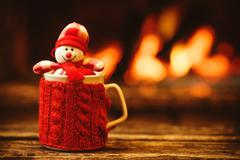Cup of hot drink in front of warm fireplace. Holiday Christmas c Stock Photos