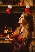 Woman with a glass of wine by the fireplace. Young attractive wo Stock Photos