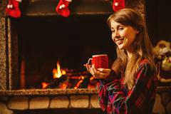 Woman with a mug by the fireplace. Young attractive woman sittin Stock Photos