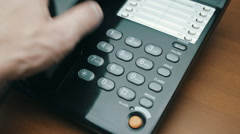 Hand picks up the phone, dials Emergency Number 911 - stock footage