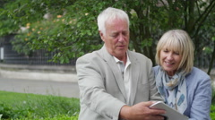 4K Portrait of happy mature couple using computer tablet in urban park area Stock Footage