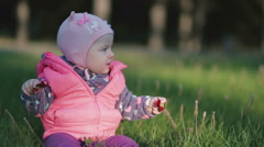 A little child sits on a green grass and playing with flowers. - stock footage