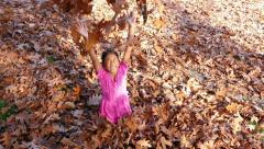Little Asian Girl Throws Crisp Autumn Leaves In The Air Stock Footage