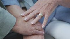4K Close up on hands of unrecognisable mature couple in love Stock Footage