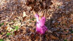 Stock Video Footage of Little Asian Girl Has Fun In Crisp Autumn Leaves