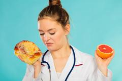 Disgusted dietitian with sweet bun and grapefruit. Stock Photos