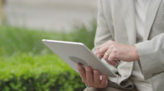 4K Portrait of happy mature man using computer tablet in urban park area. - stock footage