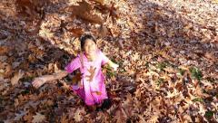 Stock Video Footage of Pretty Asian Girl Enjoys Playing In Crisp Autumn Leaves